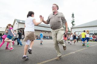 Marcus Larson/News-Register##Dayton Grade School P.E. teacher Larry Bales dances with student Elyana Russell during a performance at the Spring Showcase. Bales is retiring in June after 36 years of teaching.