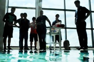 Rockne Roll/News-Register##Participants and volunteers are silhouetted against the windows of Evergreen Museum's Wings and Waves Waterpark during a SeaPerch competition last week. Students from Dayton and Warrenton spent the day racing remotely operated underwater vehicles through a course set up in the waterpark's pool.