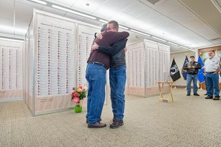 Marcus Larson##After placing a bouquet of flowers at the base of the Wall of Honor, Morey Marks and Tom McKinley hug each other. Both men lost sons in the Iraq War.