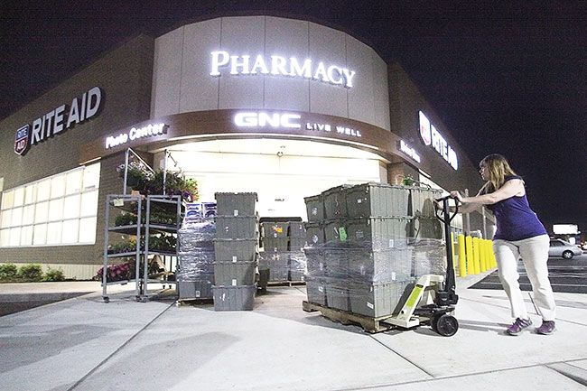 Rockne Roll/News-Register##Rite Aid's Susan Simpson prepares to unload a pallet of merchandise at the store's new location in McMinnville on Wednesday night. The store moved from its previous location at McMinnville Town Center overnight and was open for business Thursday morning.
