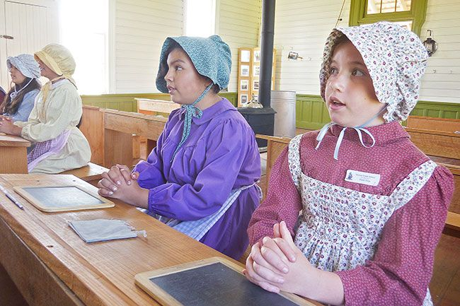 Starla Pointer/News-Register##Dressed in period costume, Maya Flake, foreground, Jocelyn Carbajal-Hernandez and other Dayton students recite a poem during Pioneer School.