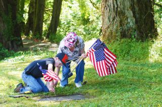 Rockne Roll/News-Register##McMinnville's Jacob McGhehey, 10,  places an American flag at the gravestone of a veteran with the help of his grandmother, Patty McGhehey, during the South Yamhill Cemetery's annual cleanup Saturday, May 28.