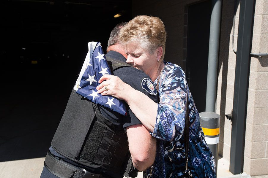 Marcus Larson/News-Register##McMinnville police officer Mike LaRue  shares a hug with Mary Fredrickson, whose recently deceased veteran husband was the inspiration for the new flag program.