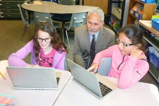 Starla Pointer / News-Register##Salam Noor, state superintendent, watches fourth-graders Jorden Woolen, left, and Nahla Nelson work on their Chromebooks. Noor heard about teaching and learning strategies, encouraging young students to think of college and other topics during his visit to Wascher Elementary.