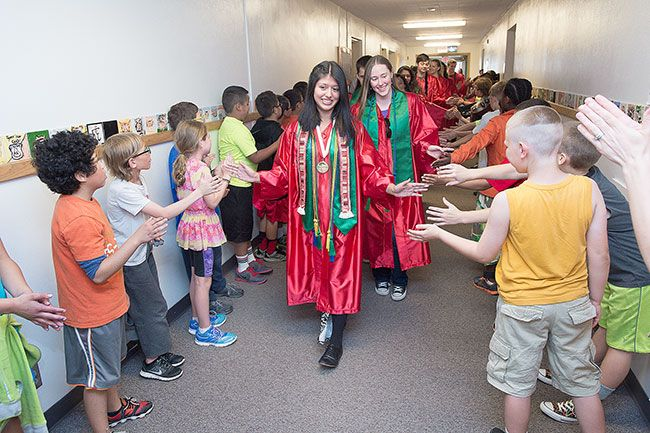 McMinnville High School student Elide Sanchez leads a group of seniors Thursday through the halls of Newby Elementary School. The class of 2015 graduates at 7 p.m. tonight.