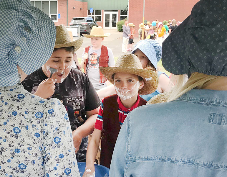 Heather Brooks/News-Register##Memorial Elementary students Benjamin Gudino (left) and Ezekiel Headings hit the first stop on the trail to prepare for the journey and chose to spend some of their money on a shave.