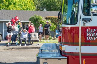 Rusty Ray/News-Register##Retired teacher and longtime fire volunteer Dan Belderrain, seated, and his family wave to firefighters and police officers who escorted Belderrain to McMinnville from a Portland hospital June 1. He spent his final week at home before dying Saturday, June 6.