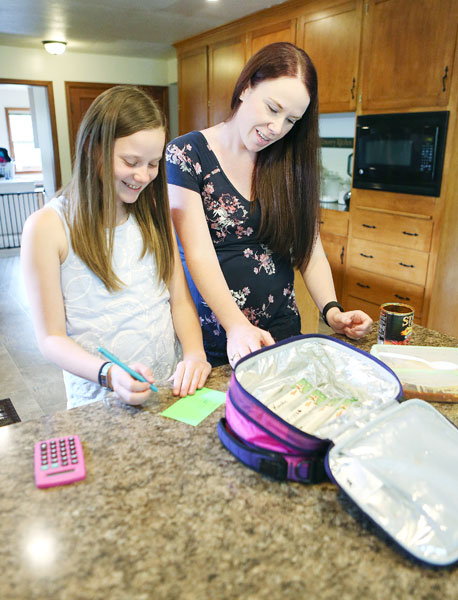 Rockne Roll/News-Register##Kaylee and her mom prepare luch for the next day at their home north of Yamhill. Kaylee must match her food intake to her insulin dosing to ensure he blood sugar remains stable.