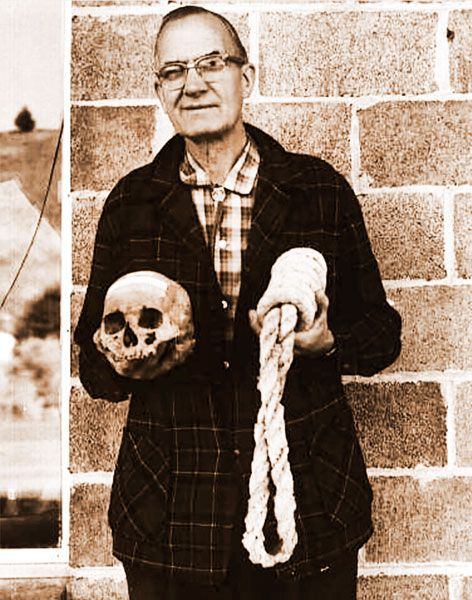 "Ben Maxwell/ Salem Public Library##Howard A. Black, curator at Grant County Museum in Canyon City, Oregon, holds the skull of Berry Way and a ""California collar,"" or noose, of the type Way was hanged with, in this 1963 photograph."
