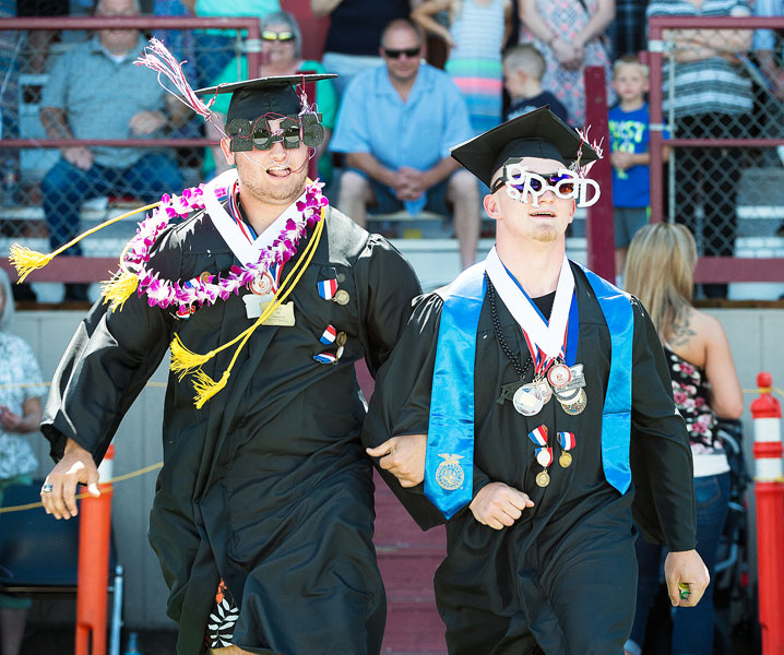 Marcus Larson/News-Register##Ceidric Stahl and Tyler Clark lock arms and skip to their seats during the graduation procession.