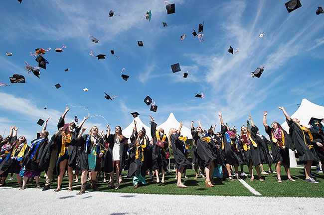Marcus Larson/News-Register##Dayton High School graduates toss their caps in the air at the end of the graduation ceremony.