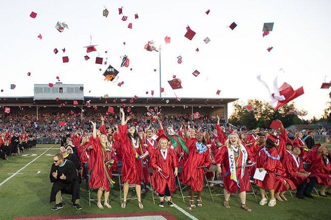 Marcus Larson / News-Register##Members of McMinnville High School s Class of 2015  toss their hats in the air to celebrate Friday night.