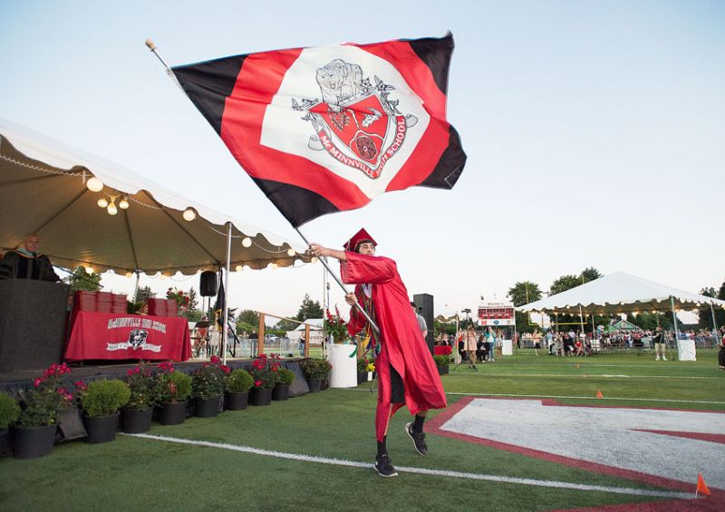 Marcus Larson/News-Register##At the conclusion of the graduation ceremony, Tanner Autencio proudly waves the McMinnville High School flag. The Class of 2015