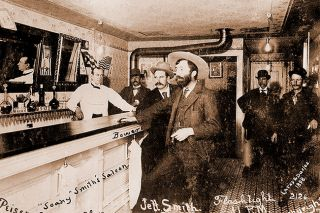 "Image: findagrave.com##""Soapy"" Smith at the bar in his saloon, ""Jeff. Smiths Parlor,"" in Skagway in 1898. Note the light bulbs; electric light was a luxury in the 1890s, especially in Alaska."