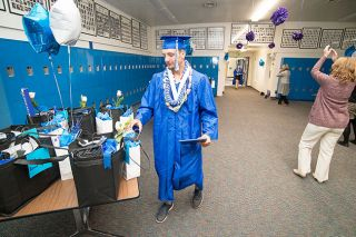 Marcus Larson/News-Register##Amity graduate Dylan Nyseth picks up a gift bag items after receiving his diploma.