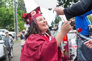 Rusty Rae/News-Register##Dayton High School graduate Yessica Rojas-Carrillo accepts a rose and a balloon, along with her diploma, from Principal Mike Solem during a parade following the commencement ceremony.