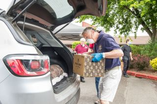 Rusty Rae / News-Register##Jim Botten loads a box of food into a client's car Friday as a part of the St. James food box giveway. In the background in the red is John Deagas. Also in the background is Father Mike Walker. This event will continue each Friday throughout June.