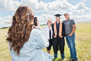 Rusty Rae/News-Register##YC High graduate Cody Brault and his parents, Tracy and Craig Brault, pose for a photo following the commence-ment ceremony held at Bailey Nurseries west of Yamhill. About 61 students graduated Sunday afternoon.