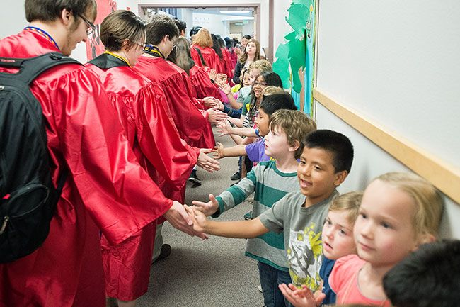 Marcus Larson / News-Register##Grandhaven Elementary students give high-fives to McMinnville High School graduates as they pass through the halls of their former school.