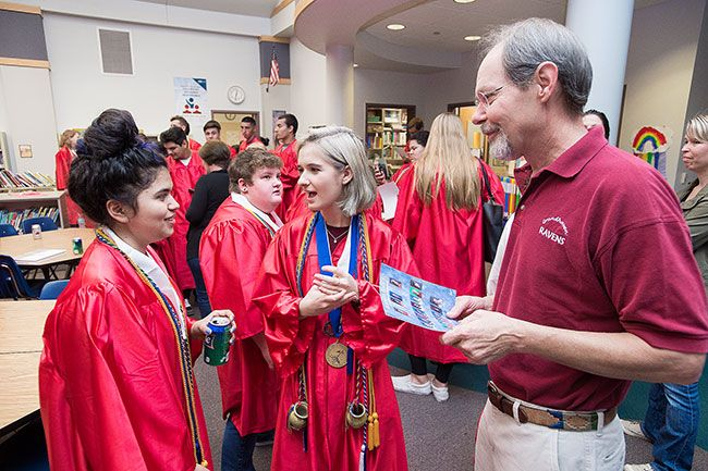 Marcus Larson / News-Register##Retired Grandhaven teacher Mark Schoenbein chats with MHS seniors Gabriella Nava, left, and Mya Clover-Owens, his former students.