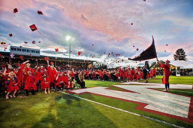 Marcus Larson / News-Register## Graduate Hallie Johnson waves the Senior 2019 flags as her classmates let their caps fly at the conclusion of the ceremony.