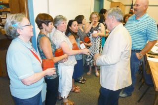 Starla Pointer/News-Register##School board members Stan Primozich and Larry Vollmer congratulate Karen Ray, Gnelia Ray and other McMinnville School District retirees at a ceremony in their honor Monday night.