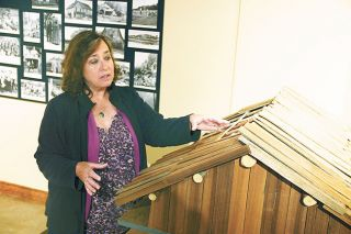 Tom Henderson/News-Register##Kathy Cole, the director of the Chachalu Tribal Museum in Grand Ronde, discusses the museum's small scale replica of a plank house. The native people of the Pacific Northwest constructed such homes from cedar trees.