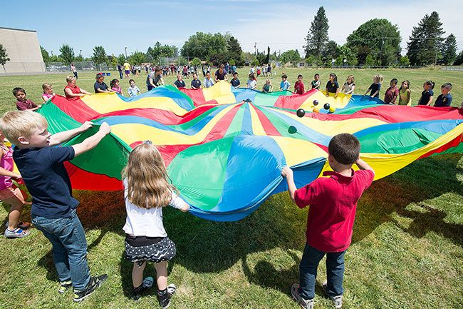 Marcus Larson/News-Register##Sue Buel Elementary School kindergartners wave a giant parachute to launch some balls in the air during Field Day. Outdoor activities are a traditional way of ending the school year.