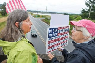 Submitted photo##Suey Linzmeier of Sheridan and Beth Dell of McMinnville protest federal immigration policies Sunday at the South Bridge Street overpass over Highway 18 near the federal prison in Sheridan.