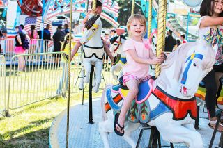Michaela Fujita-Conrads/News-Register##Hope Ulery smiles at her parents while riding a merry-go-round at the Sheridan Days Festival on Saturday,