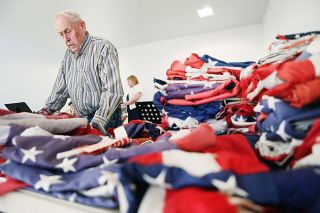 Rockne Roll / News-Register##American Legion member Marv Worden sorts through flags submitted for retirement.