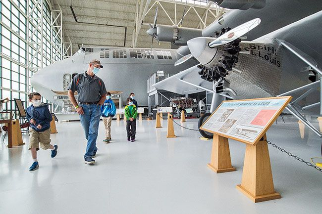 Marcus Larson/News-Register##On the first day of Evergreen Aviation Museum's reopening, James Geyer and his four grandchildren, from left, Ryan Cover, Boman Geyer, Nicky Geyer, and Grace Geyer tour the wide variety of planes on display.