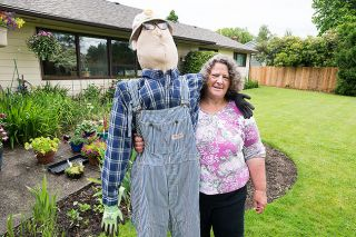 Marcus Larson/News-Register##Rhonda Robins poses with the friendly scarecrow she made to resemble her dad, Milt Robins, who loved to garden. His overalls, shirt and glasses adorn the scarecrow.