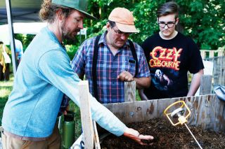 Rockne Roll/News-Register##Clay Wesson, left, shows his recently started compost pile to Joe and Nicholas Bernards during Zero Waste McMinnville's Compostpalooza event held Saturday, June 16, at the McMinnville Grange.