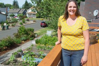 "Rockne Roll/News-Register##Hannah DeMaster grows flowers and vegetables in raised beds in her front yard. Her three children ""enjoy watching things grow,"" she said."