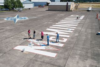 Marcus Larson / News-Register##The Boy Scouts of local troop 260 work to repaint the white lettering of the McMinnville at the municipal airport in June. Repainting of the airport compass, top left, was set for a later date.
