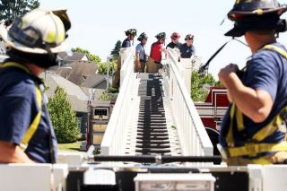 Rockne Roll/News-Register##McMinnville firefighters familiarize themselves with the turntable controls of the department's new Pierce ladder truck during a training exercise Wednesday in McMinnville. The new truck vastly exceeds the capabilities of the 35-year-old Seagraves ladder truck it replaces.