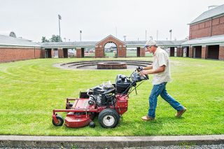 Marcus Larson/News-Register##Linfield facilities worker John Holland mows the grass near the athletic facilities on campus. The campus reopened in mid-June and will look its best when the name changes to Linfield University July 1.