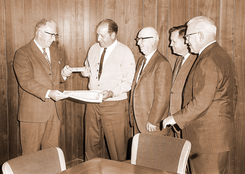 ##(June 18, 1967) A $138,000 check to finance construction of a sewage system and treatment plant in Amity is given by Frank Bartos, left, area supervisor of the Farmers Home Administration, to Mayor Jim Zupo. Looking on are City Recorder lvan Shields, Robert Jungling, manager of the Amity Branch of the U.S. National Bank, where the funds will be deposited; and William Dashney, city attorney.