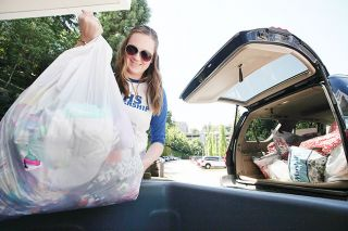 Rockne Roll / News-Register##Amity graduate Kennedy Amundson unloads a bag of toys into a donation cart at Doernbecher Children s Hospital in Portland, where she once stayed for treatment of leukemia.