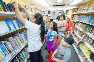 Marcus Larson/News-Register##Children browse the shelves during a bookmobile stop at Villa del Sol apartments. The McMinnville Public Library's Book Buddies program also includes educational activities.
