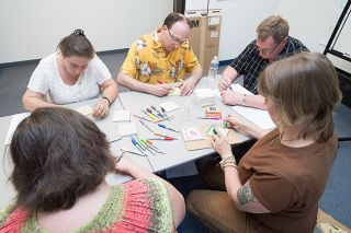 Marcus Larson/News-Register##Wellness Coordinator JoAnn Kobel, right, joins Project ABLE clients in decorating tiles to make coasters. The organization offers people with mental health issues group activities and peer support.