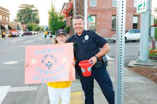 Submitted photo##Carlton Officer Rob Anderson poses with Pam, one of the Special Olympics athletes, during the Tip a Cop fundraiser June 18.