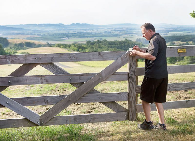 Rockne Roll/News-Register##Bailey opens the gate to the cow pasture on his property. Bailey grew up on a farm, where his family grew corn, oats and other crops, and raised livestock.
