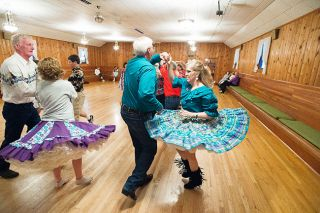 Marcus Larson/News-Register##Nate and Jennie Ramer partner at a Braids & Braves dance. Four couples form a square that moves according to directions from the caller.