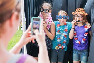 Michaela Fujita-Conrads/News-Register##Emily Sparrow, Maisie Riddle and Allison Shaver pose in the photo booth set up at the Carlton Fun Days Festival.