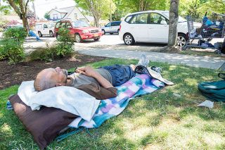 Marcus Larson/News-Register##A homeless man who gave his name as Albert lays down on a makeshift bed on the lawn of the First Presbyterian Church in McMinnville in June.