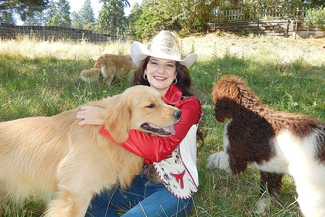 Emily Hoard/News-Register##Piscitelli plays with golden retriever, Stetson, and poodle, Abbie, two of the dogs
