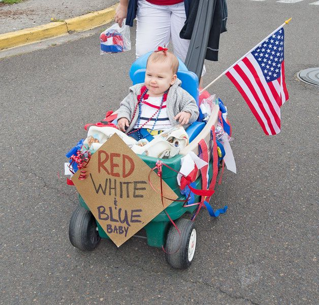 Marcus Larson/News-Register##Emory Rojas, 8 months, rides in her all-American push cart during the Lafayette Fourth of July parade. Mom Jessica Rojas accompanied Emory on the route from Wascher School to Joel Perkins Park.