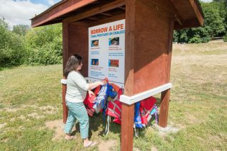 Marcus Larson / News-Register##Nathalie Hardy, who helped organize the construction of a life jacket kiosk at Rogers Landing in Newberg, hangs donated jackets in place. They may be borrowed free of charge.